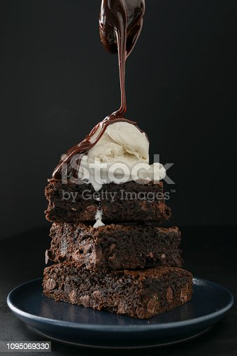 An extreme close up vertical photograph of hot fudge being poured over a stack of freshly baked whole wheat  brownies.Isolated on black.