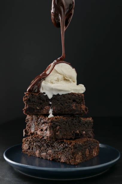 Pouring Hot Fudge On Brownies stock photo