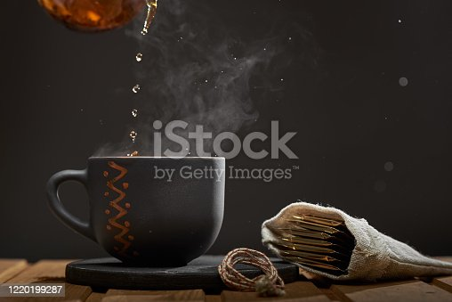 Horizontal shot of pouring hot tea into a clay Cup on a dark background. Steam rises from the Cup.