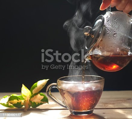 Pouring hot tea into a cup on black background, close up