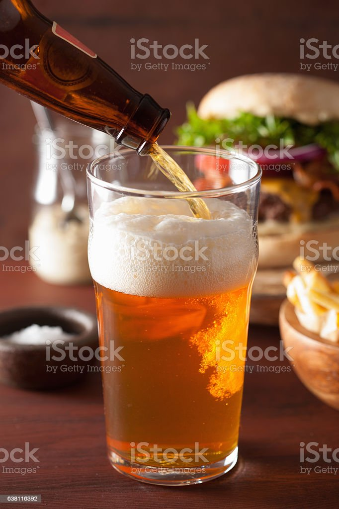 pouring india pale ale beer into pint glass and fastfood stock photo