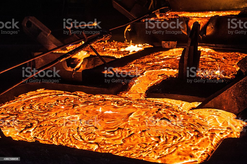 Pouring liquid titanium slag from arc furnace stock photo