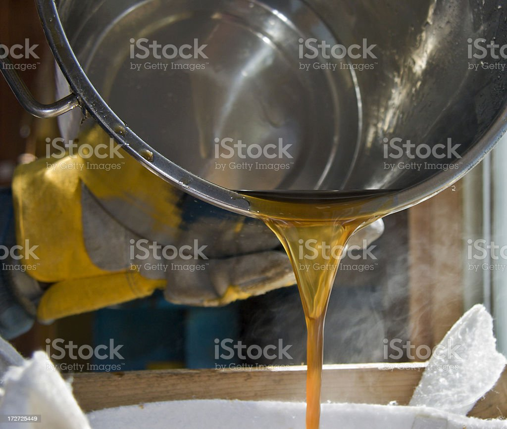 Pouring maple syrup from bucket into strainer stock photo