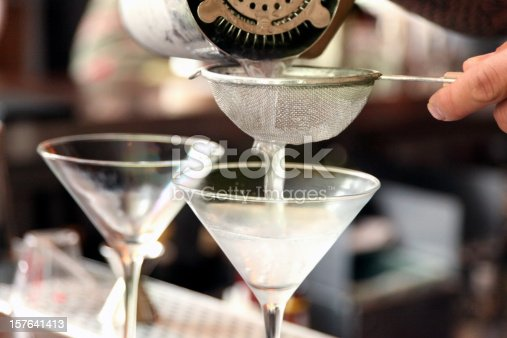 a bartender pouring martinis into chilled glasses through a small wire mesh strainer.