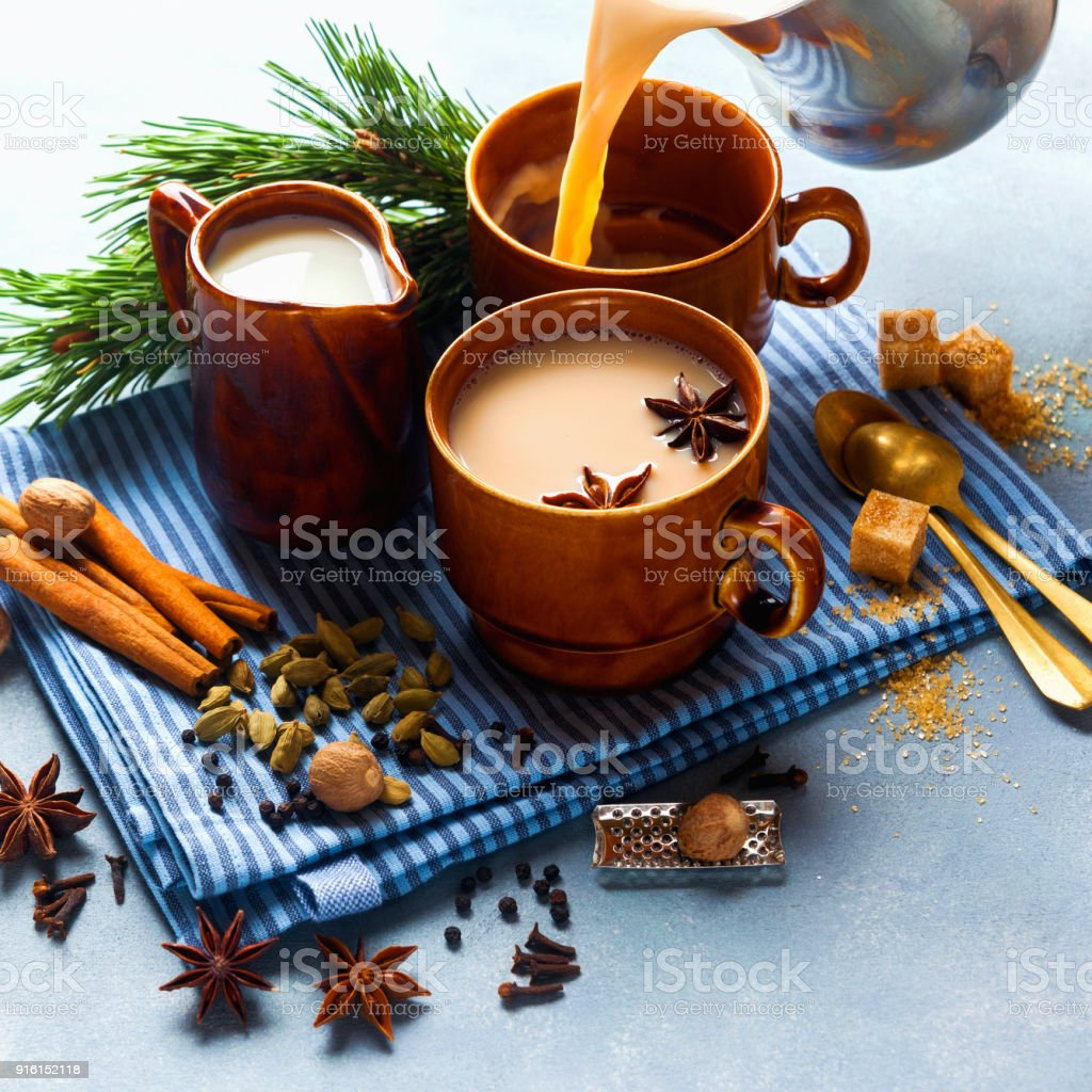Pouring Masala tea chai latte traditional hot Indian teatime ceremony sweet milk with spices, herbs organic infusion healthy beverage in porcelain cup n blue table background. royalty-free stock photo