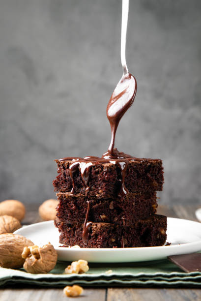 Pouring melted chocolate on brownies with a spoon stock photo