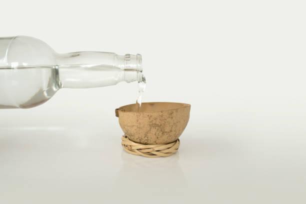 verter la mezcal en una copa de madera tradicional. - mezcal fotografías e imágenes de stock