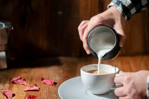 pouring milk froth into coffee stock photo