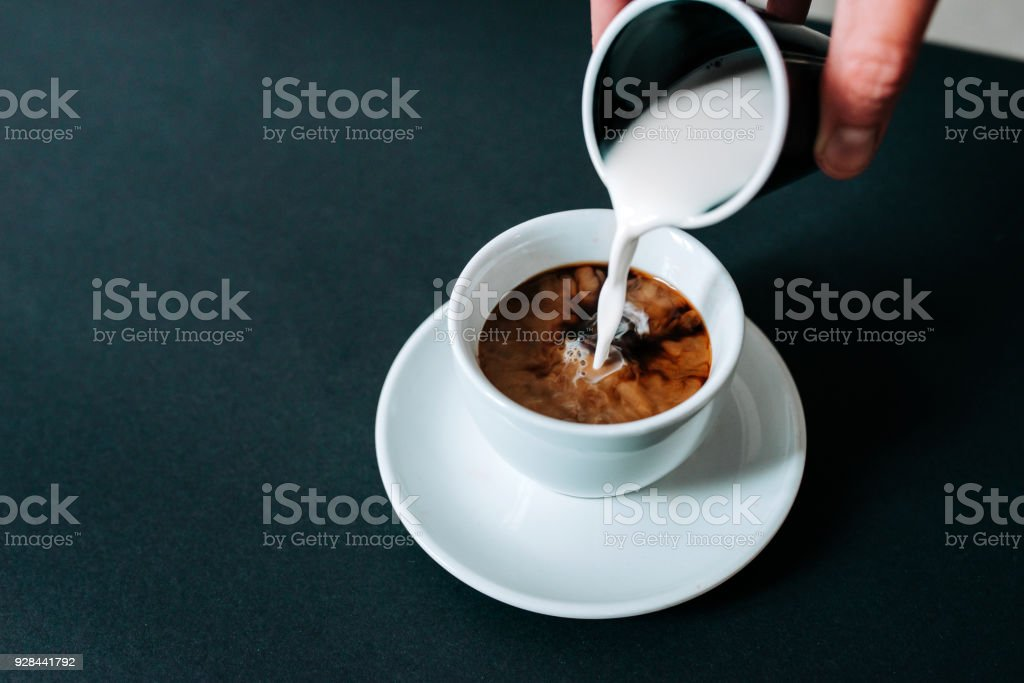 Pouring milk in black coffee. Isolated background. stock photo