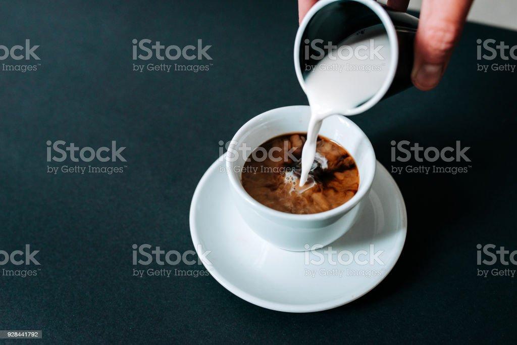Gießen die Milch in schwarzen Kaffee. Isolierte Hintergrund. – Foto