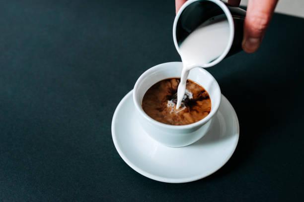 pouring milk in black coffee. isolated background. - coffee foto e immagini stock