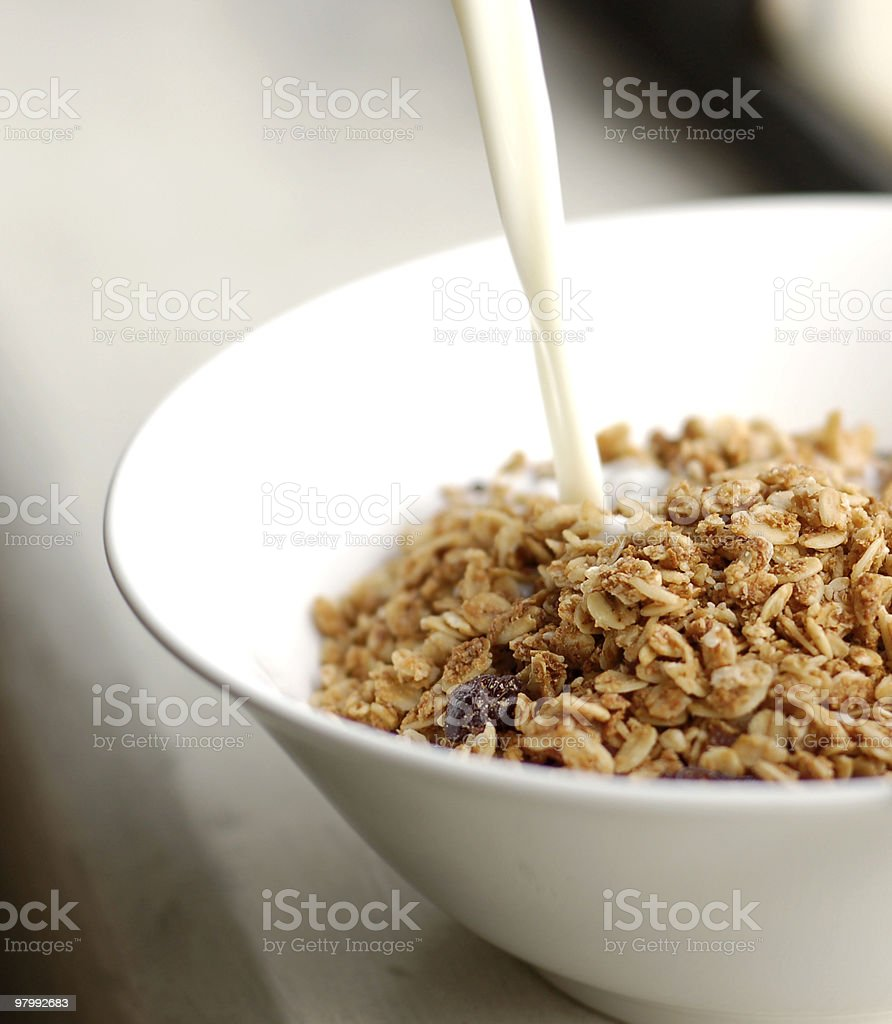 Pouring milk in museli bowl royalty free stockfoto