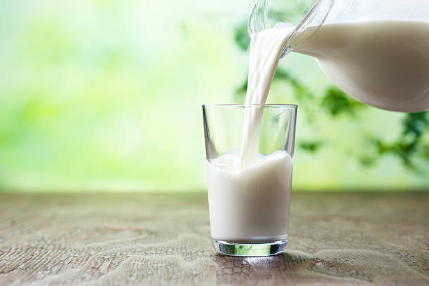 pouring milk in the glass on the background of nature. - kalcium bildbanksfoton och bilder