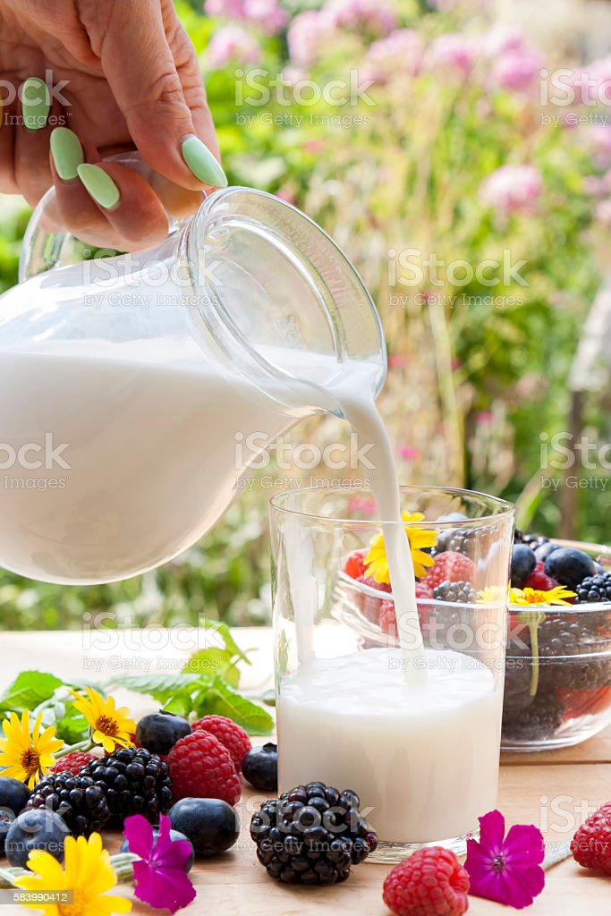 Pouring milk in the glass on the table royalty-free stock photo