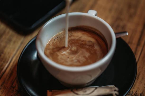 Pouring milk into coffee stock photo