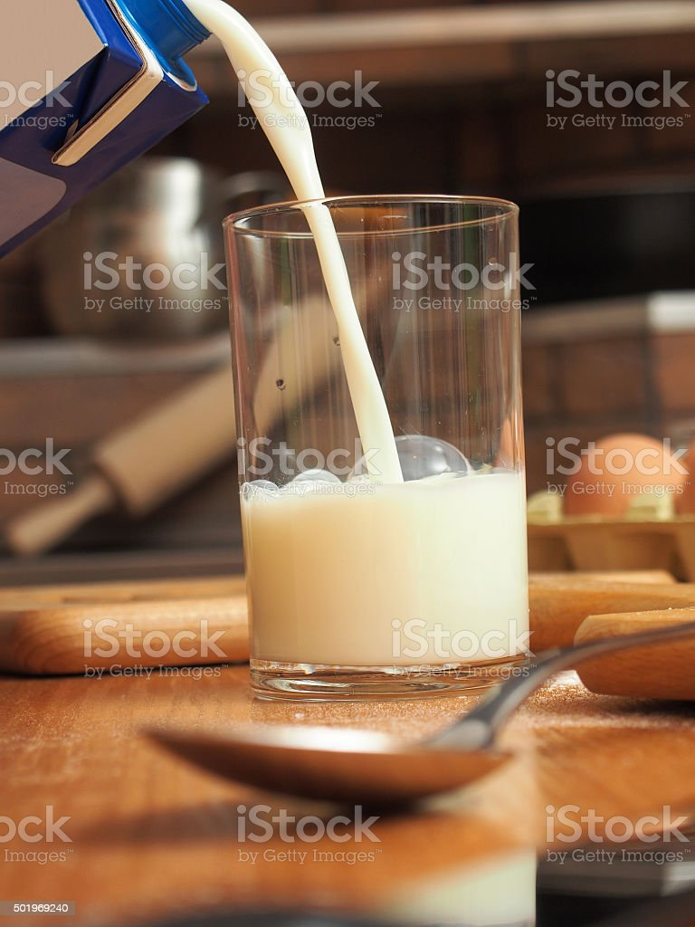 Pouring milk into glass. Making yeast pancakes (crepes). stock photo
