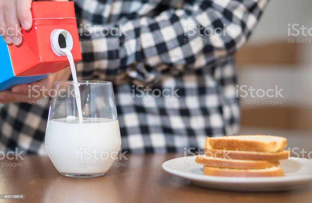 pouring milk into glass stock photo