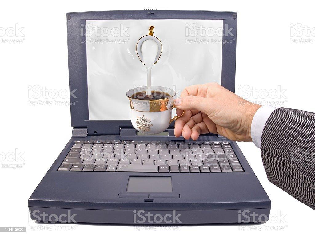 pouring milk to tea on notebook stock photo