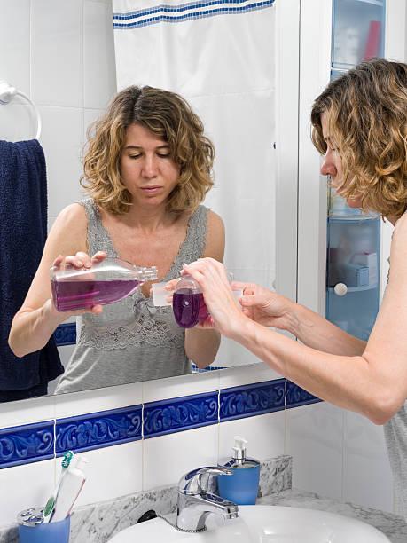 eingießen mundspülung in eine tasse - lange duschvorhänge stock-fotos und bilder