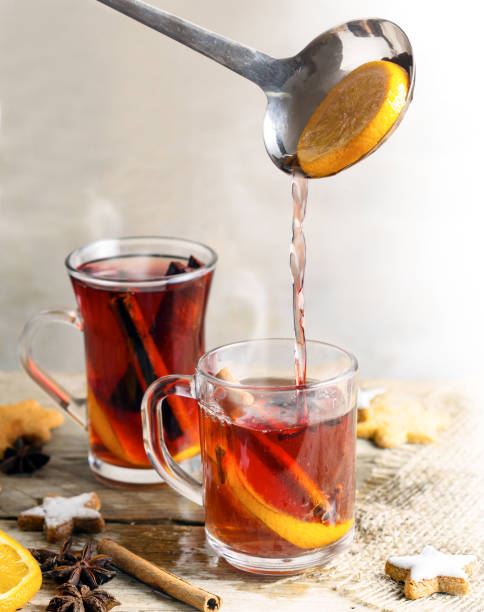 pouring mulled wine in glass mugs, christmas cookies and spices like orange, cloves, star anise and cinnamon, rustic wooden table, bright background, vertical - mulled wine stock photos and pictures