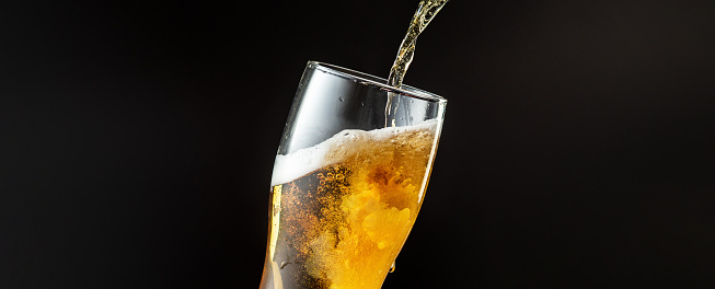 Pouring of cold and refreshing beer in glass with foam, horizontal flyer with copyspace for ad. Oktoberfest, drinks, alcohol, party concept. Brewed and crafted quality product on dark background.