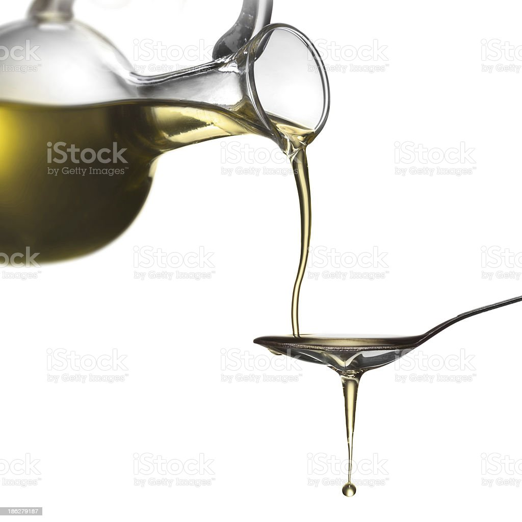 Pouring oil from jar on spoon isolated royalty-free stock photo