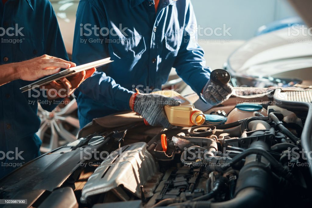 Pouring oil in engine stock photo