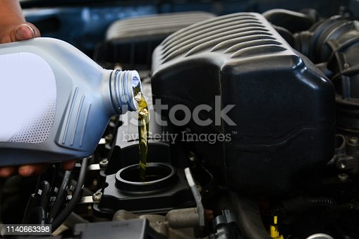 Pouring oil into the car engine, refueling, car shop