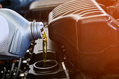 istock Pouring oil into the car engine, refueling 1142005615