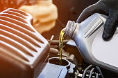 istock Pouring oil into the car engine, refueling 1142005618