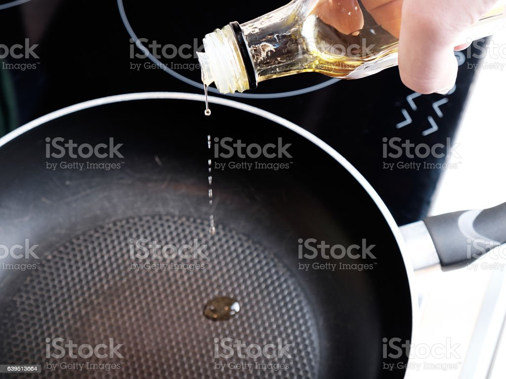 Pouring oil into the frying pan stock photo