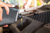 istock Pouring oil to car engine. Fresh oil poured during an oil change to a car. 1199351079