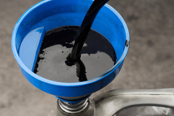 Pouring old black oil of  car engine from oil pan into bottle on top view lubrication used for recycle stock photo