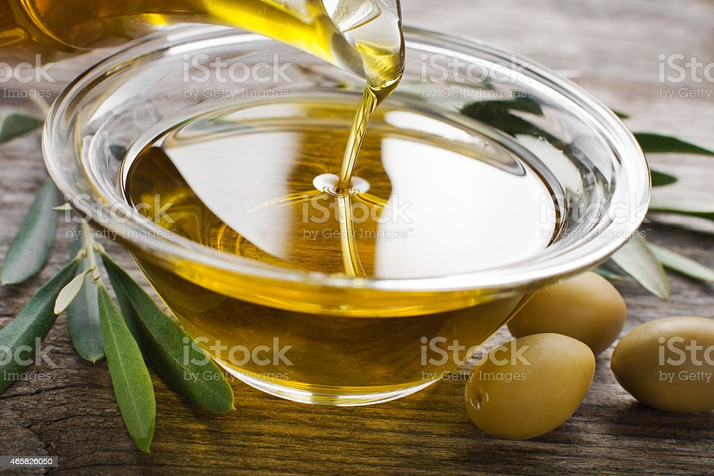 Pouring Olive oil in a bowl close-up stock photo