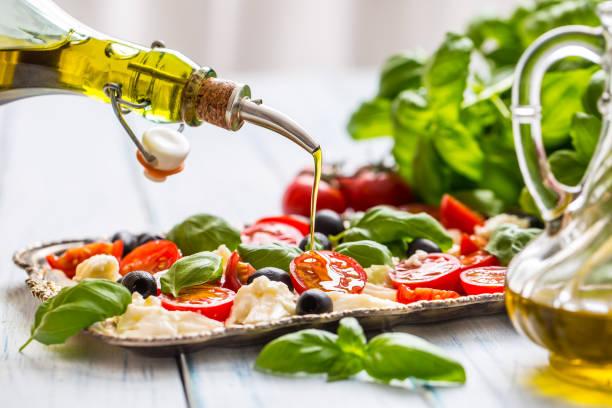 Gießen Olivenöl auf Caprese Salat. Gesunde italienische und mediterrane Mahlzeit – Foto