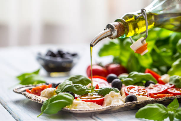 Pouring olive oil on caprese salad. Healthy italian or mediterranean meal stock photo