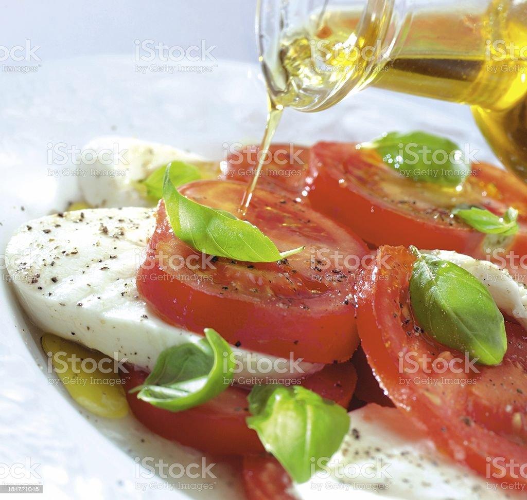 pouring olive oil over tomatoes & mozzarella royalty-free stock photo