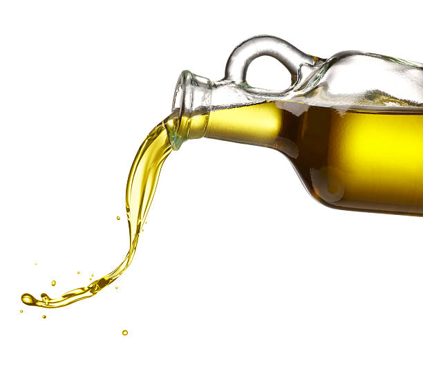 pouring olive oil pouring olive oil from glass bottle against white background olive oil stock pictures, royalty-free photos & images