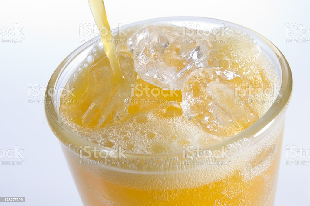 Pouring Orangeade Into A Glass Of Ice stock photo