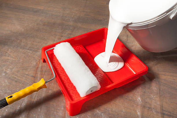 Pouring Paint In an Empty Paint Tray stock photo