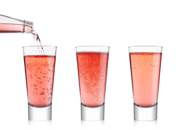 Pouring pink soda lemonade from bottle to glass stock photo