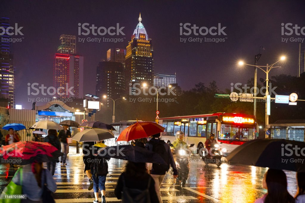 City view of Taipei downtown and rain, with people crossing the...