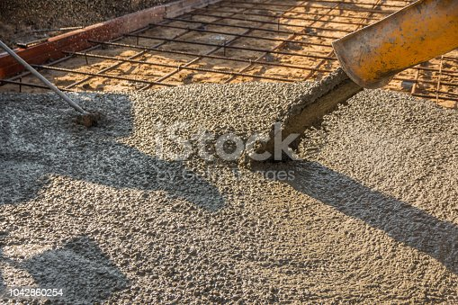Pouring ready-mixed concrete after placing steel reinforcement to make the road by mixing mobile the concrete mixer.