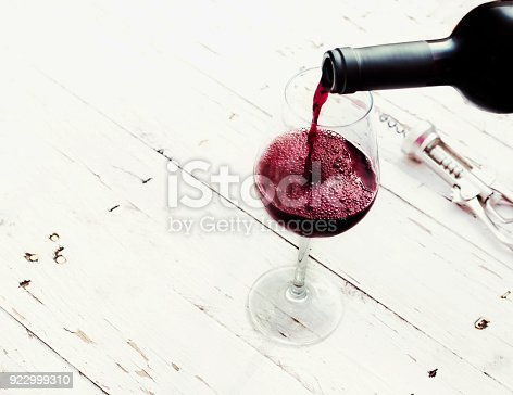 istock Pouring red  wine from bottle in wine glass on vintage white wooden table  with copyspace. 922999310
