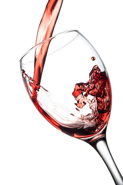Pouring red wine in a wine glass, isolated on a white background stock photo