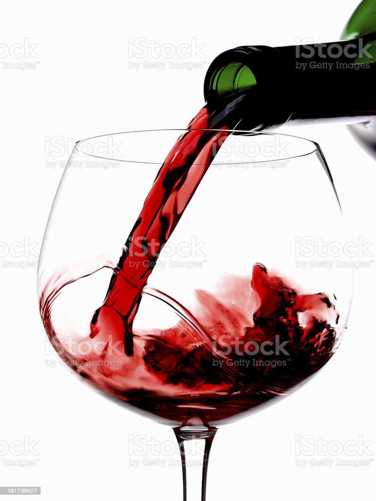 Pouring red wine in glass goblet isolated on white royalty-free stock photo