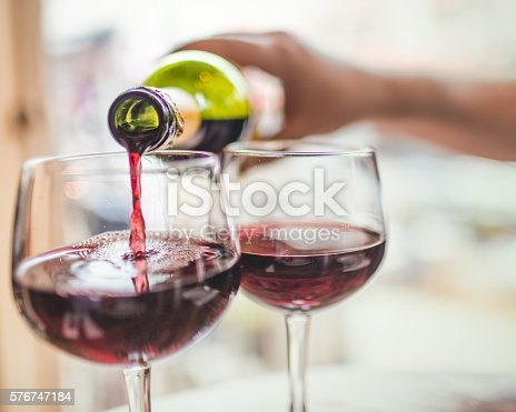 Unrecognizable man pouring red wine in two glasses.