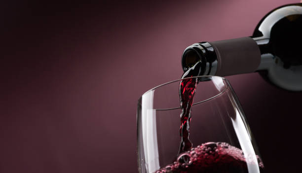 Pouring red wine into a wineglass stock photo