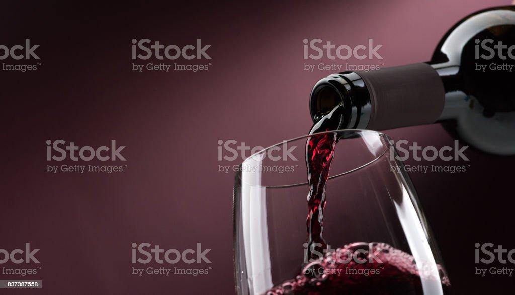 Verser le vin rouge dans un verre à vin - Photo