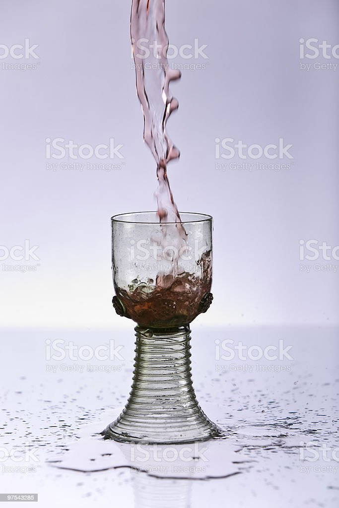 Pouring red wine into an old glass royalty-free stock photo